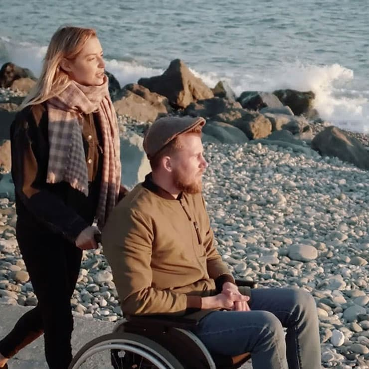 A woman and a man in a wheelchair strolling by the ocean