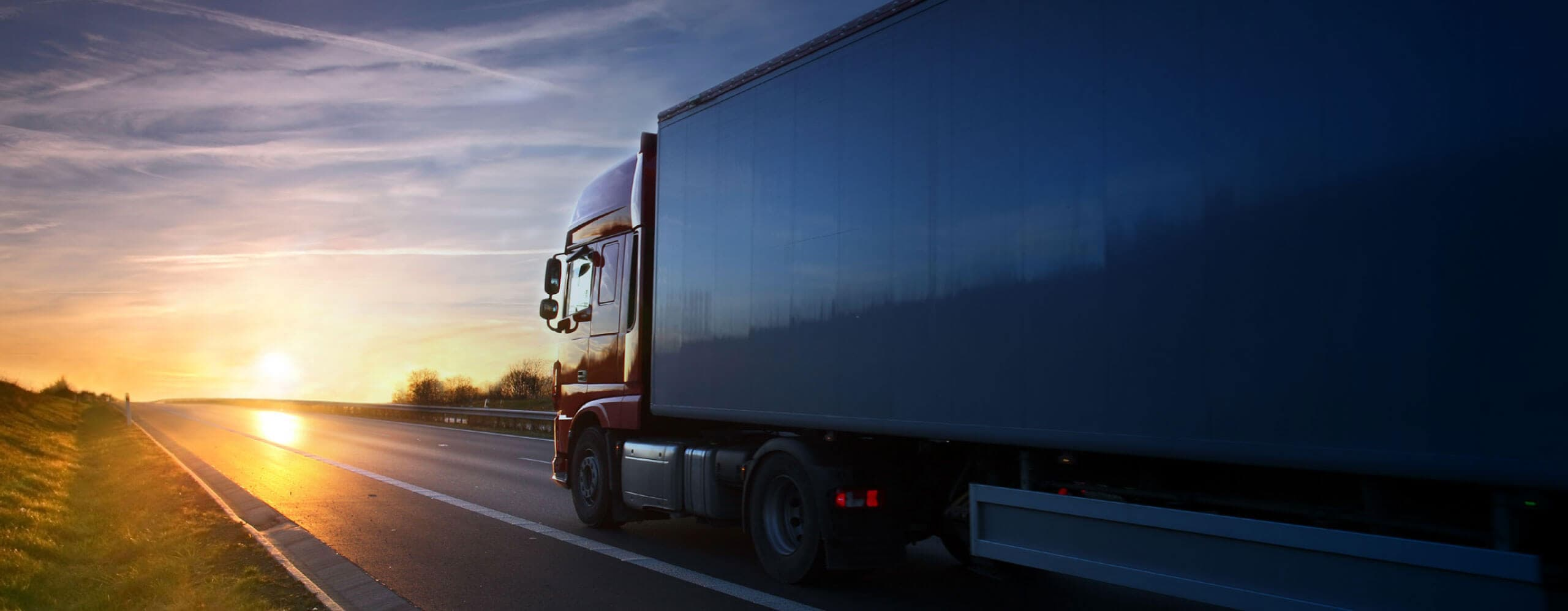 A transport truck drives towards us as the sun sets behind it.