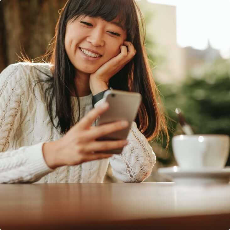 Une femme qui sourit en regardant son téléphone.