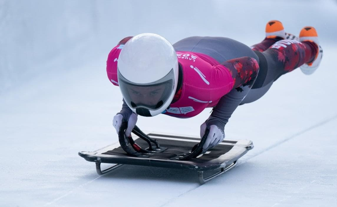 A speed skater rounding a corner on the ice.