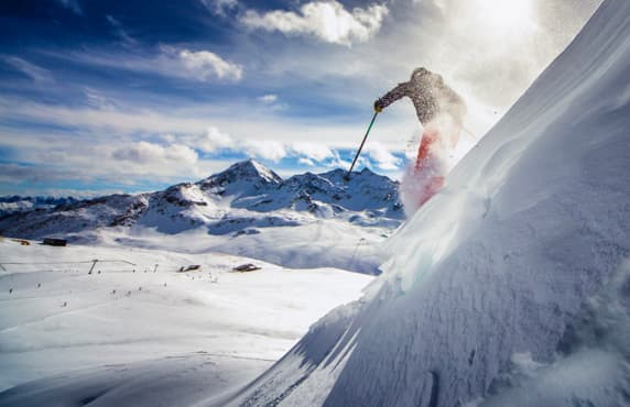 A skier going down a steep mountain slope.