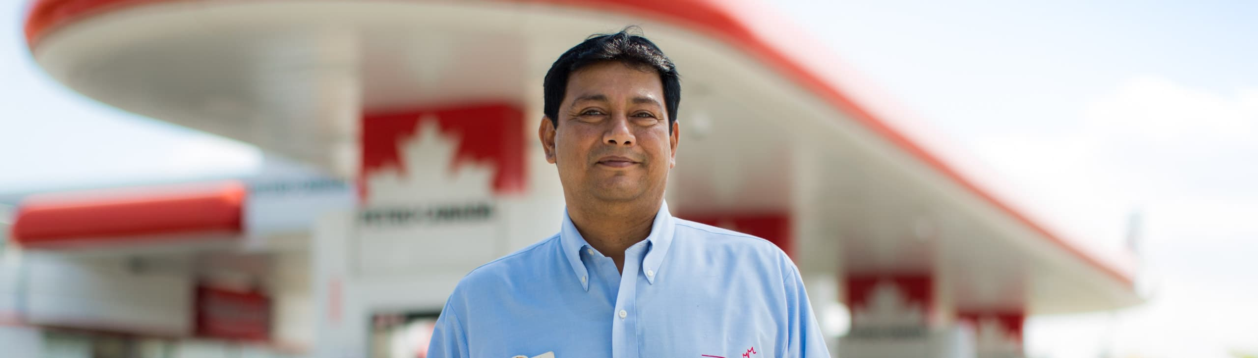 A Petro-Canada retail operator standing in front of his store.