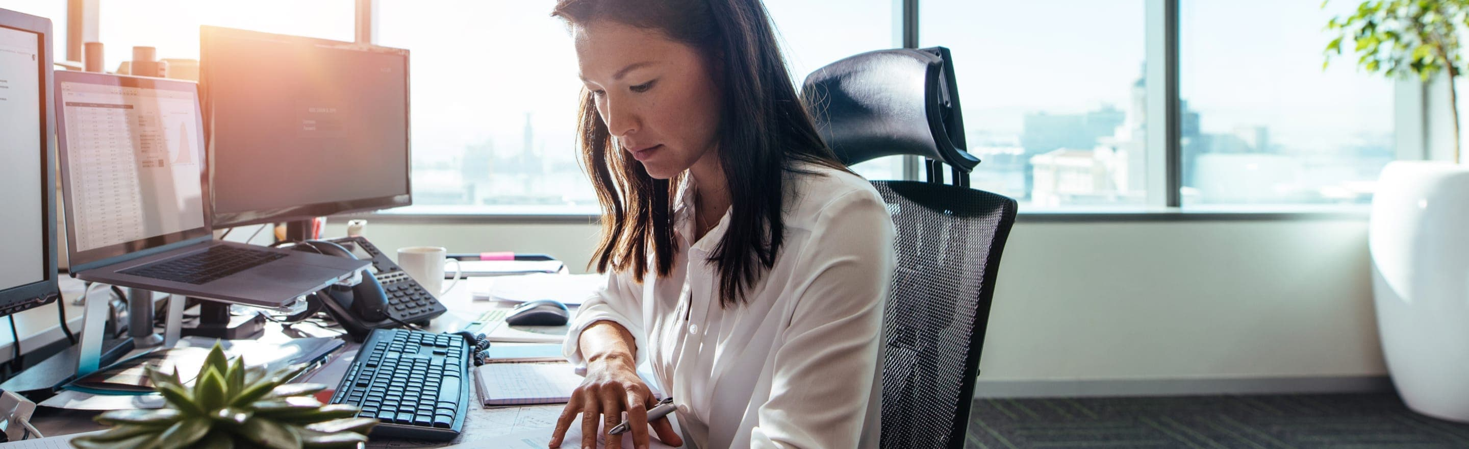A business woman working at her desk in an open, light-filled office.