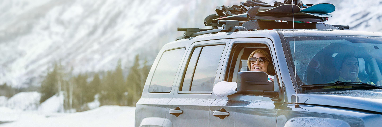 Un VUS avec des planches à neige sur le toit devant une montagne enneigée.
