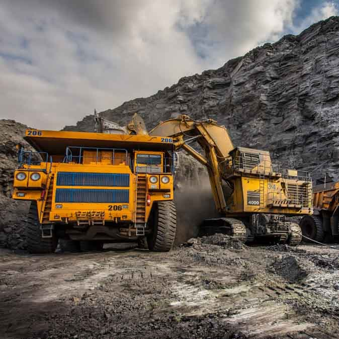 Large yellow mining trucks and equipment in a mine.